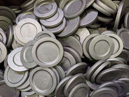 full frame pile of gray steel forgings after shot blasting - close-up natural heavy industrial pattern with selective focus
