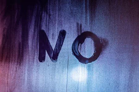 the word no handwritten on night wet window glass surface