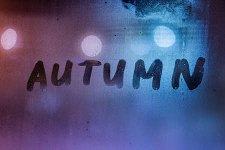 the word autumn handwritten on night wet window glass surface