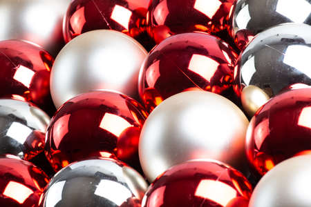 full frame background of red, silver and white mirror balls close-up with selective focus