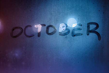the word october handwritten on night wet window glass surface Фото со стока
