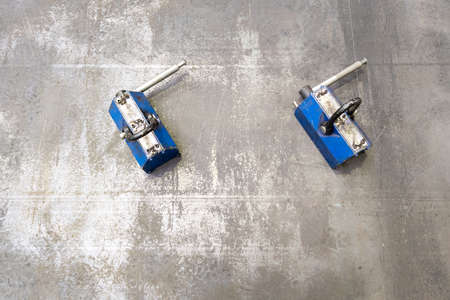 Pair of blue industrial lifting magnets on flat sheet metal surface. Фото со стока