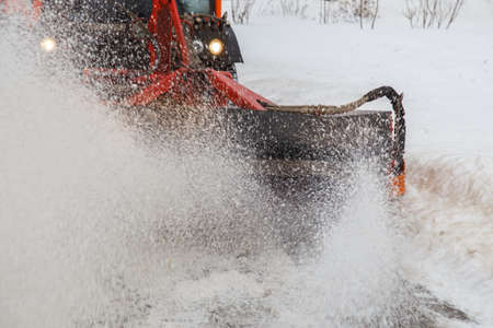 Snow cleaning. Snow removal tractor clearing snow from pavement with special round spinning brush,