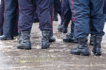 Russian police officers legs in black ankle boots - closeup with selective focus