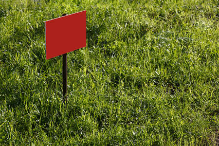 blank red sign mockup on green lawn background - close-up with selective focus Reklamní fotografie