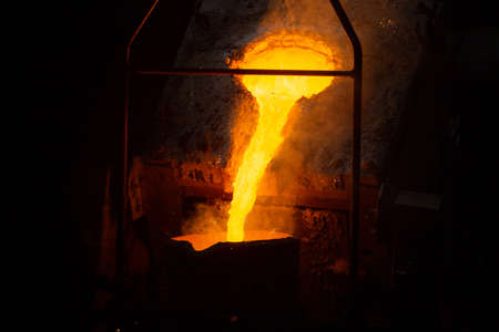 a process of ladle filling with molten hot steel from furnace with smoke - close-up with selective focus Stock Photo