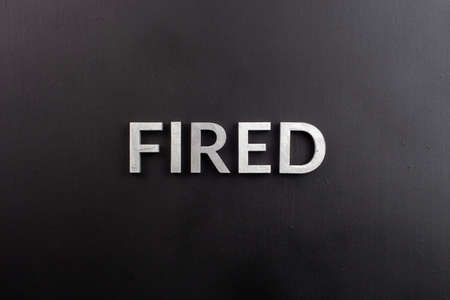 the word fired laid with white brushed metal letters on flat black surface