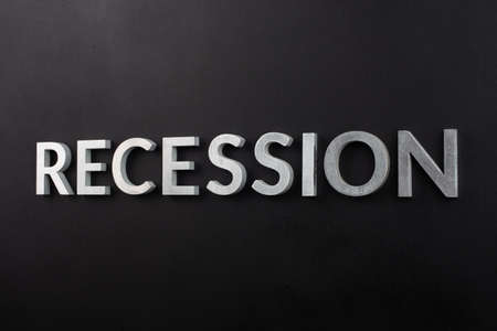the word recession laid with white brushed metal letters on flat black surface