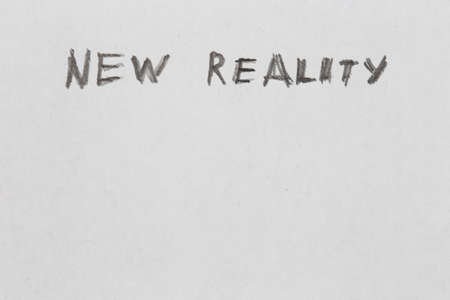 the words new reality handwritten on blank white paper with pencil Stock Photo