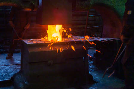 close-up picture of hot steel manual forging process with big mechanical hammer machine Stock Photo