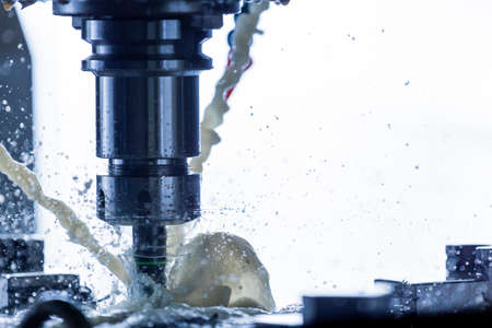 Close-up view of vertical cnc steel milling process with external water coolant streams, splashes and a lot of metal chips, high contrast Stock Photo