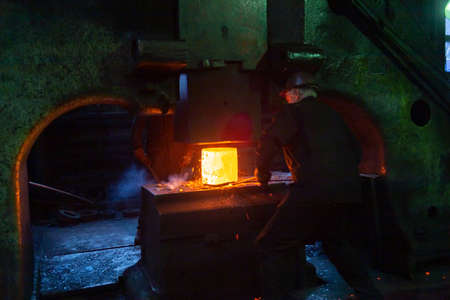 close-up picture of hot steel free forging process with big mechanical hammer machine Stock Photo