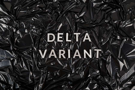 words delta variant laid with silver metal letters on crumpled black plastic bag background Stock Photo