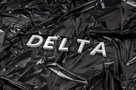 the word delta laid with silver metal letters on crumpled black plastic bag background in diagonal perspective