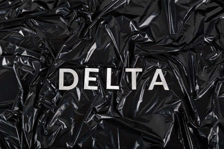 the word delta laid with silver metal letters on crumpled black plastic bag background Stock Photo