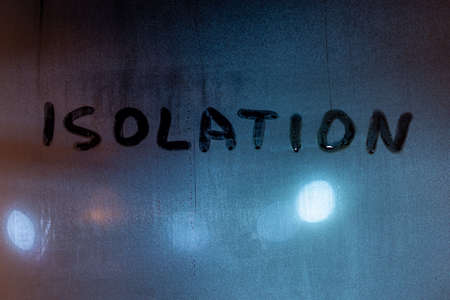 the word isolation handwritten with finger on foggy night window glass with blurry street lights on the background Stock Photo
