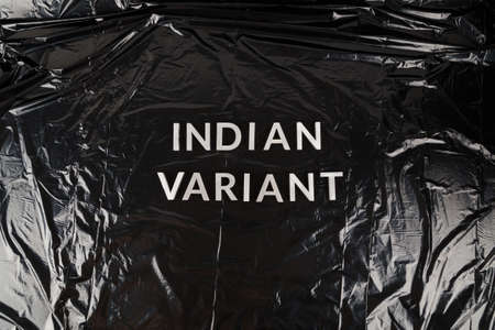 words indian variant laid with silver metal letters on crumpled black plastic bag background