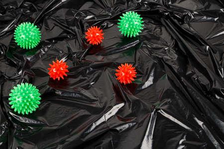 full frame abstract background of covid-19 virus models on crumpled black plastic body bag.