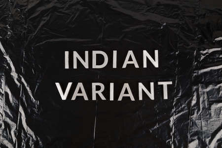 words indian variant laid with silver metal letters on crumpled black plastic bag background. Stock Photo