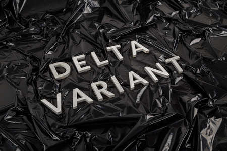 words delta variant laid with silver metal letters on crumpled black plastic bag background in diagonal perspective. Stock Photo