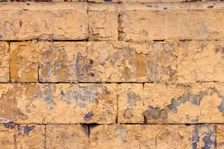 peeled off old orange paint on flat rough brick wall surface - full frame background and texture
