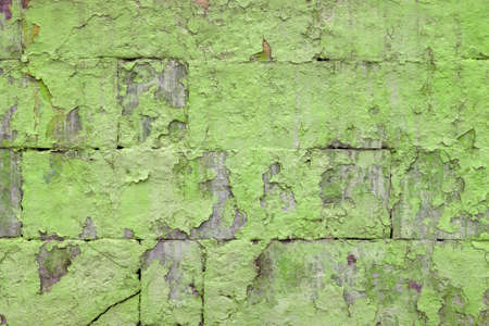 peeled off old green paint on flat rough brick wall surface - full frame background and texture