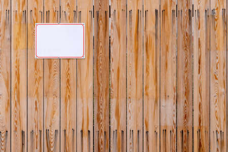 wooden fence of vertical planks with screwed blank white plate
