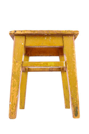 Old wooden stool with yellow peeling paint. Loft style chair isolated on a white background.