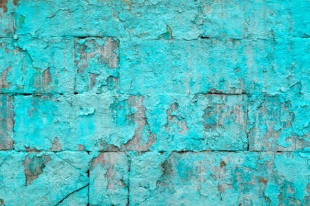 peeled off old turquoise paint on flat rough brick wall surface - full frame background and texture