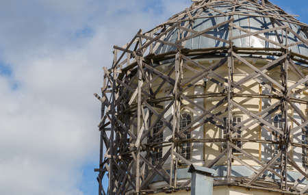 gray wood scaffolds on architectural dome at day light on blue sky with white clouds