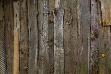 Fence from old unedged boards. Wooden croaker plate texture flat full frame background.