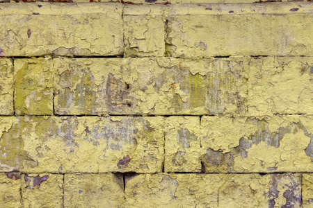peeled off old yellow paint on flat rough brick wall surface - full frame background and texture