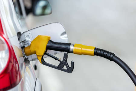 Silver car refuelling at the gas station, the concept of fuel energy