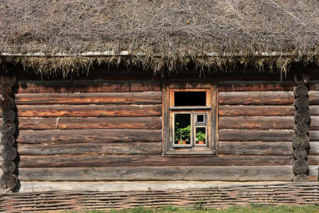 full frame background and texture of traditional russian log house with straw roof and one window Stock fotó