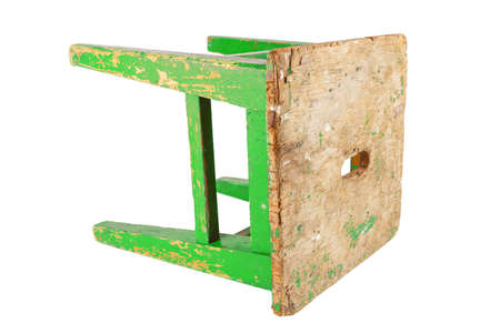 Old wooden stool with peeling lime green paint. Loft style chair isolated on a white background.