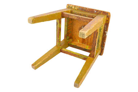 Old wooden stool with peeling ocher yellow paint. Loft style chair isolated on a white background.