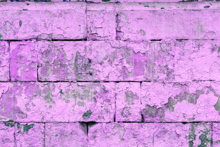 peeled off old violet paint on flat rough brick wall surface - full frame background and texture