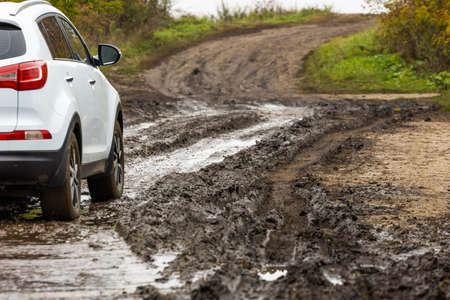 clean white suv car moving on dirt road with wet clay in front of blurry slope Stock fotó