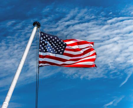American flag flying against a blue sky.