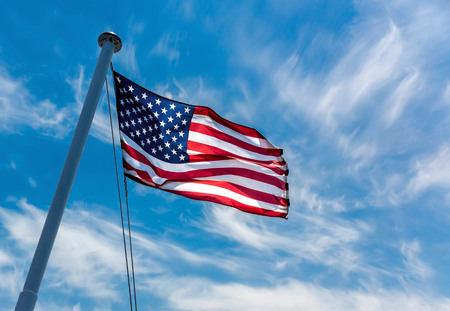 American flag flying against a blue sky.