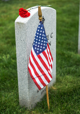American flag and Red Rose on a veterans tombstone at an American National Cemetery.