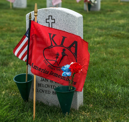 Killed in Action flag by a tombstone at an American National Cemetery. Фото со стока