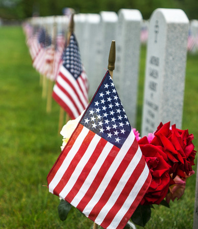 American flagz and  tombstones at an American National Cemetery. Foto de archivo