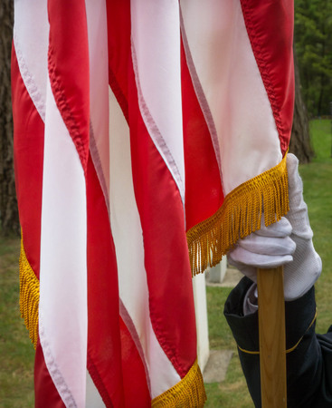 Military Honor Guard holding the staff of the American Flag at a Memoral Day ceremony.
