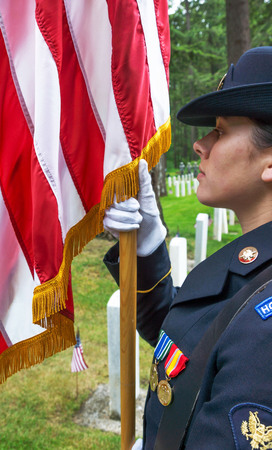 Female Military Honor Guard holding the staff of the American Flag at a Memoral Day ceremony at Ft. Lewis, Washington.  25 May, 2015.