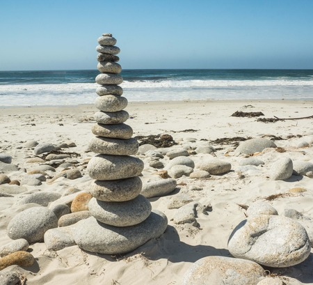 Stacked stones on a sandy beach by the Ocean. Фото со стока