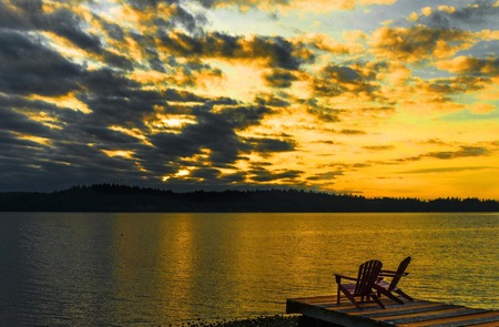 Chairs on a dock on a golden sunset evening.sunset