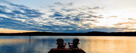 Chairs on a dock at sunset.