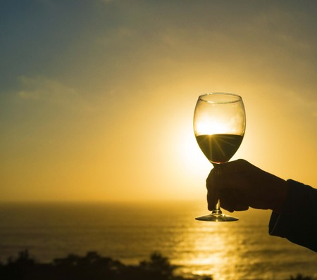 A glass of Red Wine at Sunset by the ocean. Фото со стока