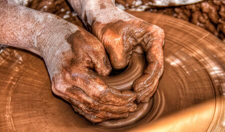 Hands of a potter shaping a vase on a potters wheel.